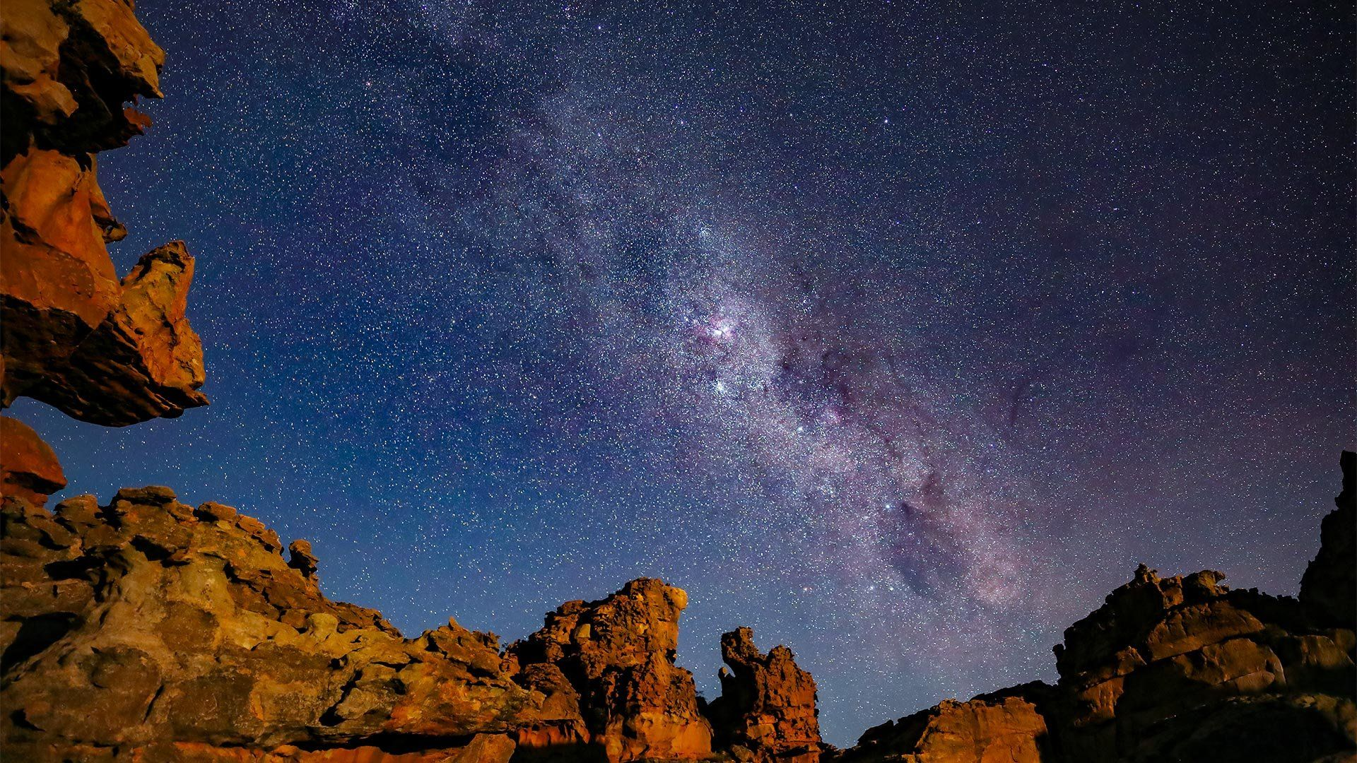 The Milky Way in a star-filled sky, above rugged cliffs in the foreground.